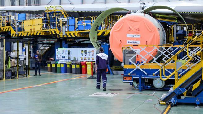 Dos operarios de la Compañía Airbus durante labores de mantenimiento a un avión de la compañçía en la planta de Airbus en Getafe, en Madrid a 27 de noviembre de 2019.