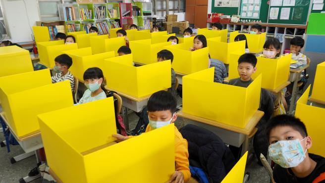 Estudiantes en Taiwan con bloques para evitar el contagio de coronavirus en sus pupitres.