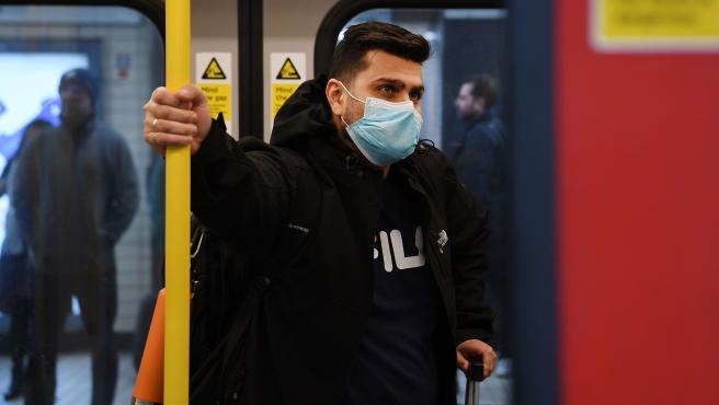 Un hombre con una mascarilla en el metro de Londres.
