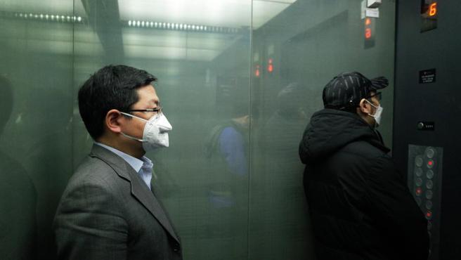 Dos personas con mascarillas por el coronavirus COVID-19, en un ascensor de Pekín, China.