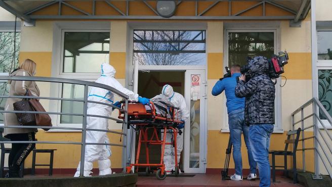 Personal médico con ropa protectora trasladan a un paciente al Hospital Universitario de Zielona Gora, en Polonia.
