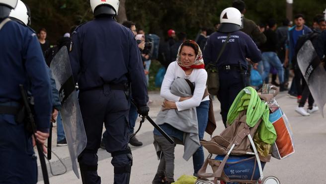 Agentes de policía griegos apartan a un grupo de refugiados en Mytilene.