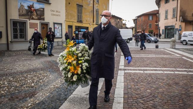 Imagen del asistente a un funeral en Bergamo, Italia, cubierto con una mascarilla.