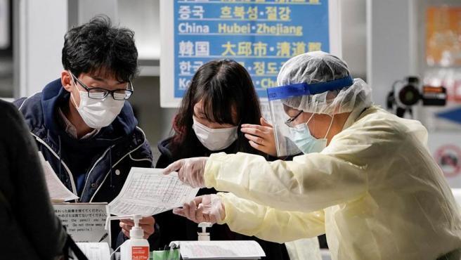 Pasajeros procedentes de Seúl, Corea del Sur, reciben instrucciones al llegar al aeropuerto internacional de Narita, en Japón, antes de ser puestos en cuarentena por el coronavirus COVID-19.