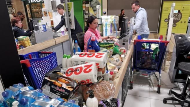 Una cajera pasa los productos de un cliente tras vaciar su carro, en otro supermercado de Madrid.