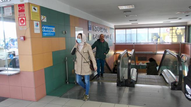 Una mujer, con mascarilla por el coronavirus, sale del intercambiador de transportes de Plaza de Castilla.