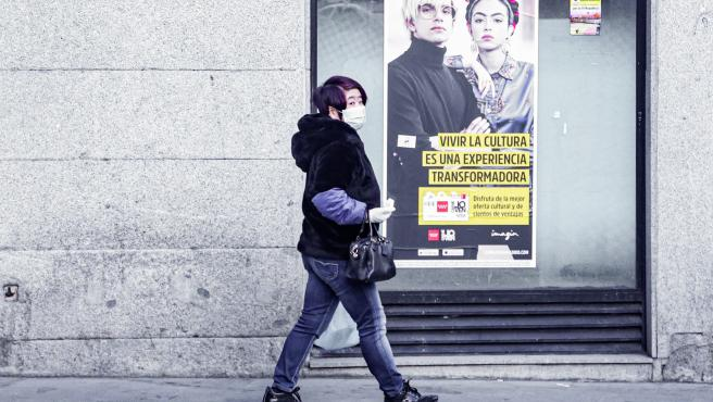 Una mujer con mascarilla por una calle de Madrid.