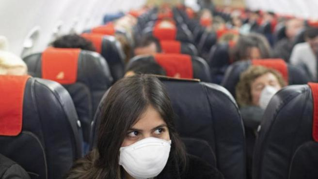 Una pasajera viaja con mascarilla en un avión