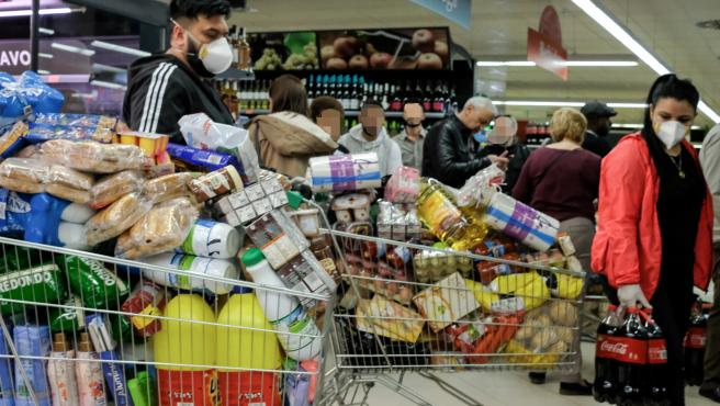 Decenas de personas cargadas con provisiones esperan para poder pagar en un supermercado.