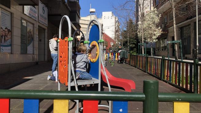 Un niño juega en una zona infantil vacía en una calle del centro de Madrid.
