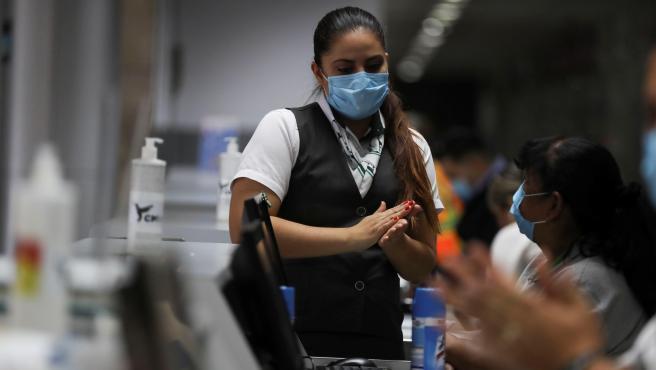 Trabajadores con mascarillas y geles desinfectantes.