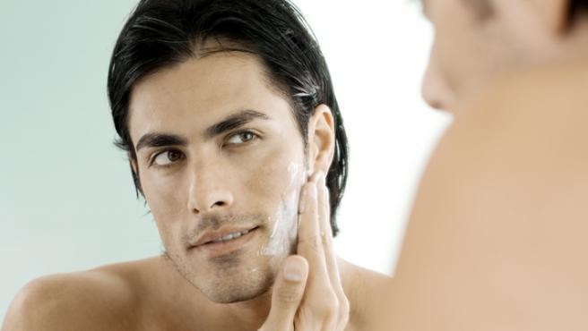 Imagen de archivo de un hombre cuidándose la piel.