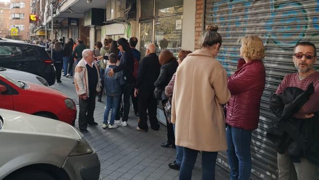 Varias personas hacen cola para entrar a un estanco en Madrid.