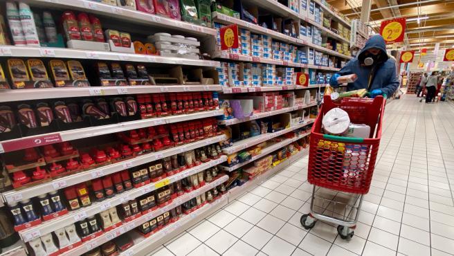 Un hombre cubierto con una mascarilla coge productos de las estanterías de un supermercado de Madrid.