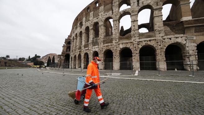 Un barrendero con mascarilla frente al Coliseo de Roma.