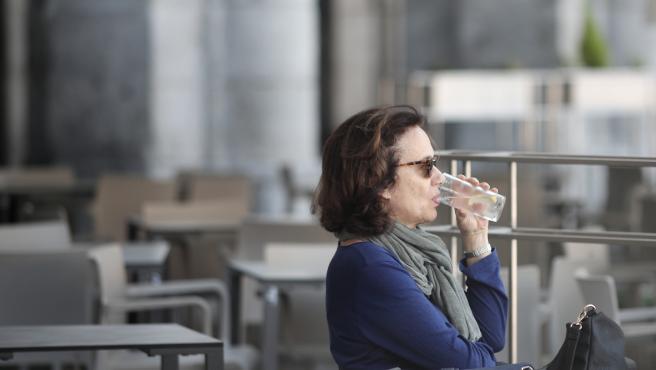 Una mujer toma un refresco en una terraza.