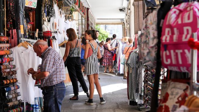 Varios turistas realizan compras en una de las tiendas ubicada en una calle cercana a la Plaza Mayor de Madrid.