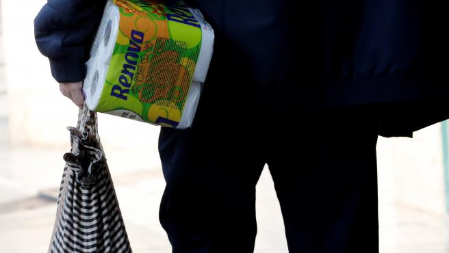 Un hombre carga un paquete de papel higiénico este sábado en Valencia.