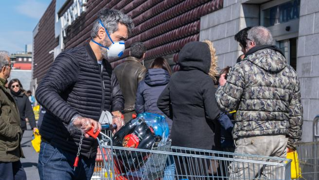 Imagen de archivo de un hombre haciendo la compra con mascarilla para protegerse del coronavirus.