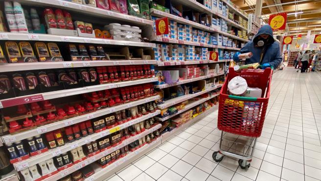 Un hombre cubierto con una mascarilla coge productos de las estanterías de un supermercado de Madrid