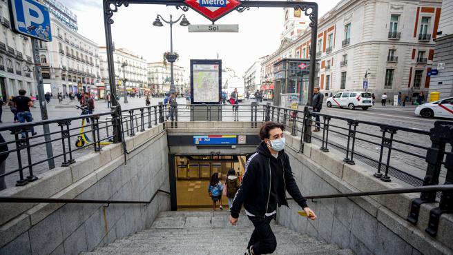 Un joven sale del Metro de la Estación Sol con mascarilla