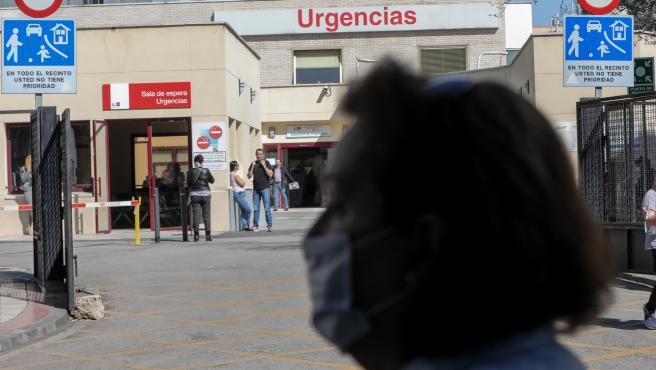 Una mujer protegida con mascarilla pasea cerca de la puerta de Urgencias del Hospital Gregorio Marañón, un día después de que el presidente del Gobierno, Pedro Sánchez, declarase el Estado de Alarma debido a la crisis del coronavirus en España, en Madrid