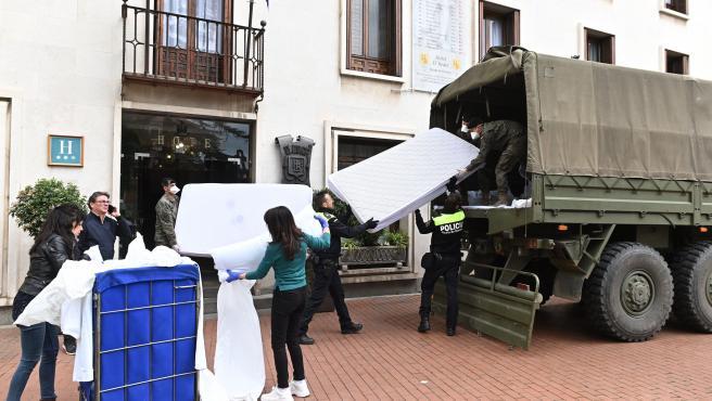 Soldados de la Brigada Paracaidista (Bripac) cargan colchones de un hotel del centro de Alcalá con destino al Hospital de Henares, Madrid.