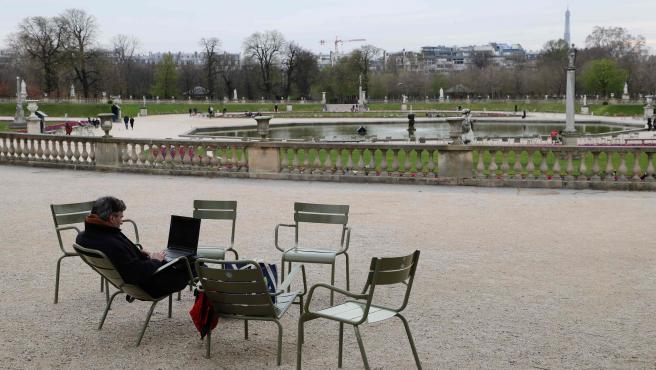 Un hombre trabaja con un portátil, en los Jardines de Luxemburgo de París, prácticamente vacíos por el coronavirus.