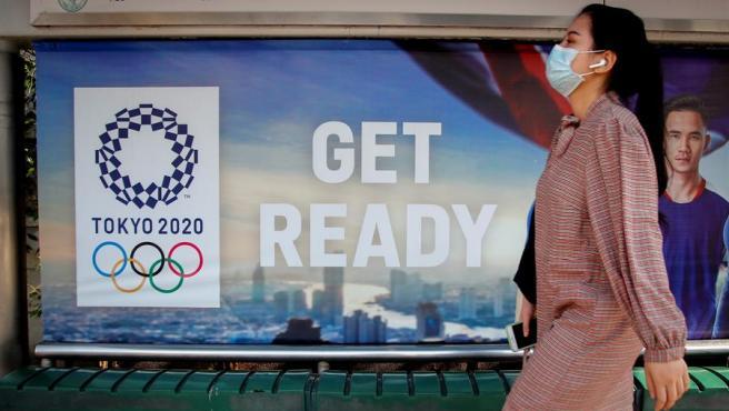 Una mujer pasa delante de un cartel de los Juegos Olímpicos.
