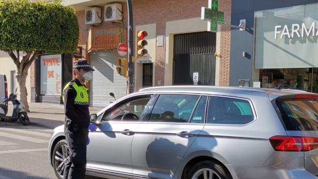 Un agente de la Policía Local de Rincón de la Victoria (Málaga) informando a un conductor de las medidas del estado de alarma ante el COVID-19