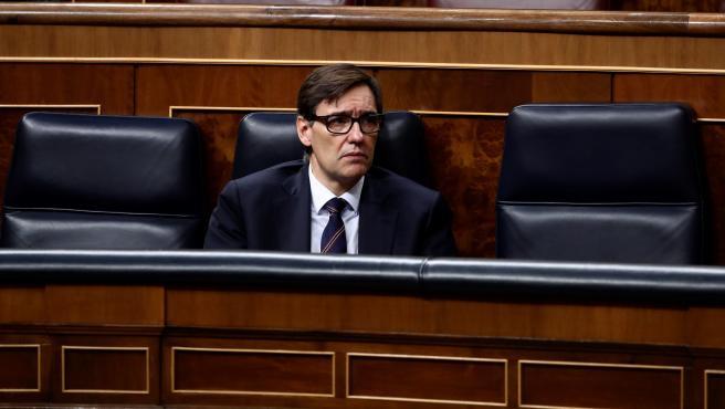 El ministro de Sanidad, Salvador Illa, escucha, en el Congreso, la intervención del presidente del Gobierno, Pedro Sánchez, durante el pleno extraordinario por el coronavirus.