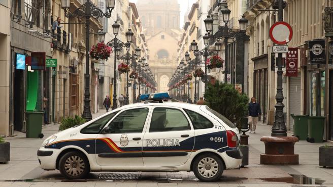 Un coche de policía aparcado en el centro de Zaragoza durante el tercer día laborable del estado de alarma por coronavirus