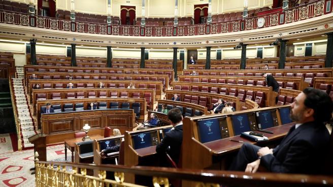 Algunos de los diputados en sus escaños en el Congreso, casi vacío por el Coronavirus
