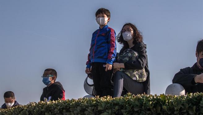 Varias personas con mascarillas por el coronavirus COVID-19 observan aviones aparcados en el aeropuerto internacional de Pekín, tras la decisión del Gobierno de poner en cuarentena a todos los viajeros que lleguen a China desde otros países.