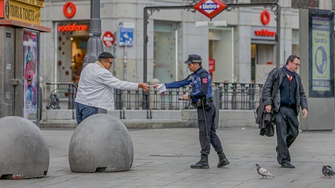 Un policía municipal de Madrid pone una multa a un viandante por no respetar la cuarentena en Madrid.