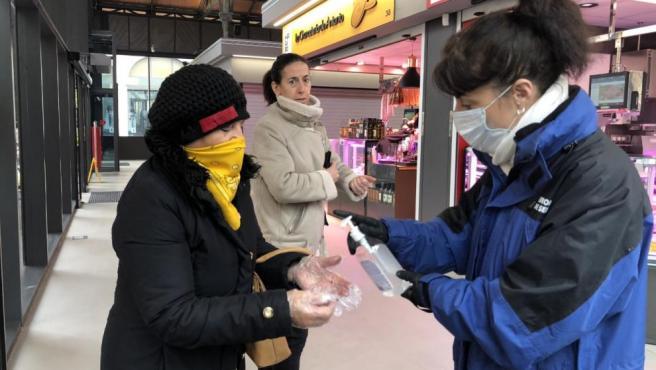 Una clienta del Mercado Central de Lanuza se lava las manos con jabón desinfectante antes de comprar.