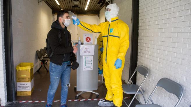 Un paramédico con ropa protectora toma la temperatura para clasificar a los pacientes que llegan al Centro Médico y de Diagnóstico Kilicare en Bruselas, Bélgica.