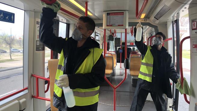 Dos trabajadores desinfectando el tranvía.