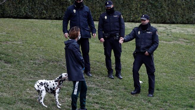 Varios policías conversan con una mujer que saca a pasear a su perro en un parque.