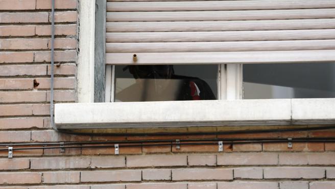 Un hombre con mascarilla en la ventana de un edificio Madrid
