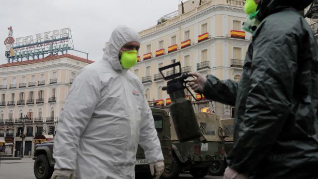 Miembros de la Unidad Militar de Emergencias (UME) desinfectando la Puerta del Sol en Madrid.