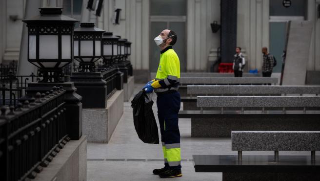 Un trabajador de la limpieza trabaja protegido con una mascarilla.