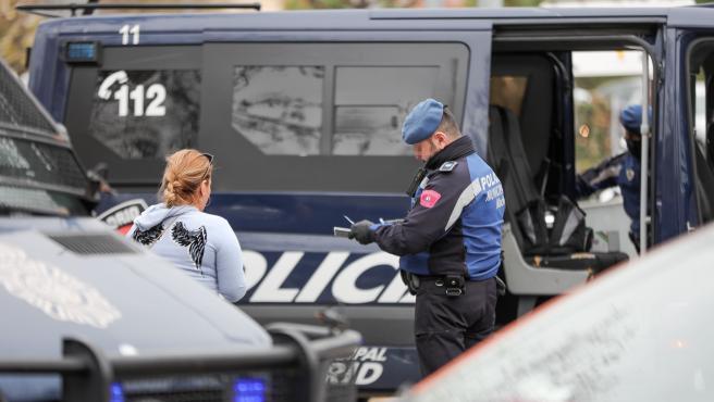 Un agente de la Policía Municipal multa a una mujer por un viaje no justificado en un control policial en la Glorieta del Marqués de Vadillo durante el sexto día de confinamiento por coronavirus en el país, en Madrid (España) a 20 de marzo de 2020.