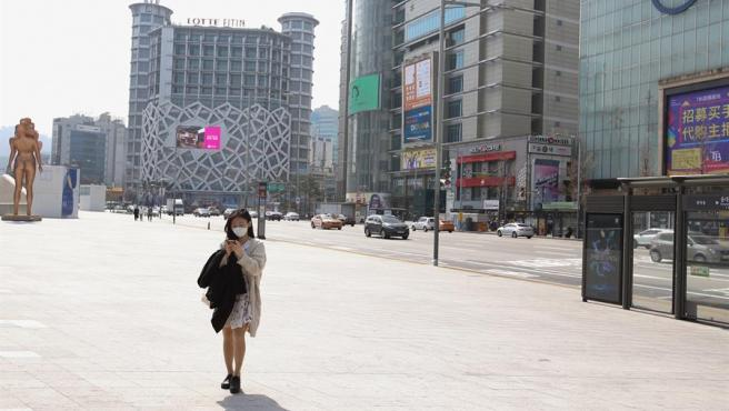 Una mujer con una mascarilla consulta su teléfono en una calle de Seúl, Corea del Sur, prácticamente desierta por las medidas para contener la expansión del coronavirus COVID-19.