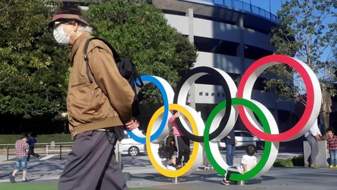 Un hombre con una mascarilla por el coronavirus COVID-19 pasa junto a unos anillos olímpicos instalados en Tokio, Japón.