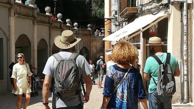 Turistas paseando por una calle céntrica de Palma.
