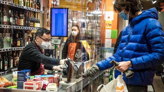 Un hombre paga a través de una mampara en un comercio en París.