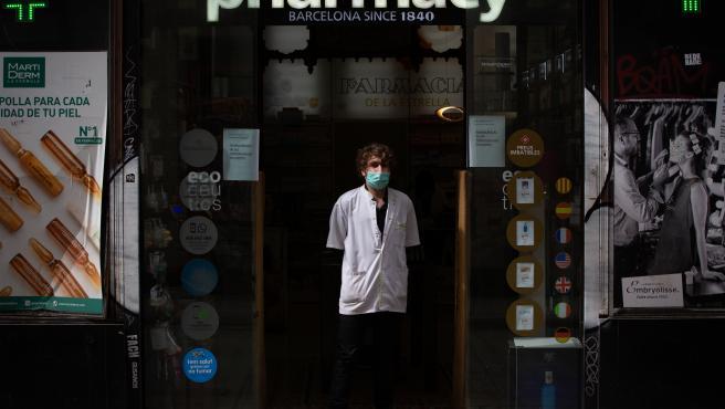 Un farmacéutico protegido con mascarilla en la puerta de una farmacia durante el segundo día laborable del estado de alarma por el coronavirus, en Barcelona (España), a 17 de marzo de 2020.