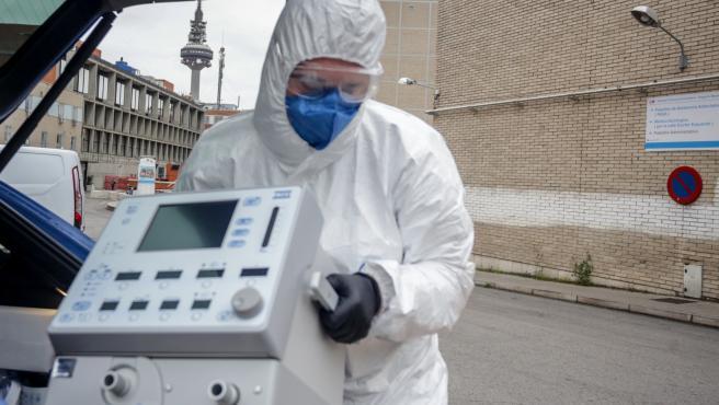 Un técnico protegido con un traje, guantes y mascarilla en el Hospital Gregorio Marañón, saca un respirador del maletero de su coche antes de montarlo en el Hospital, elemento imprescindible para muchos pacientes enfermos de coronavirus, en Madrid