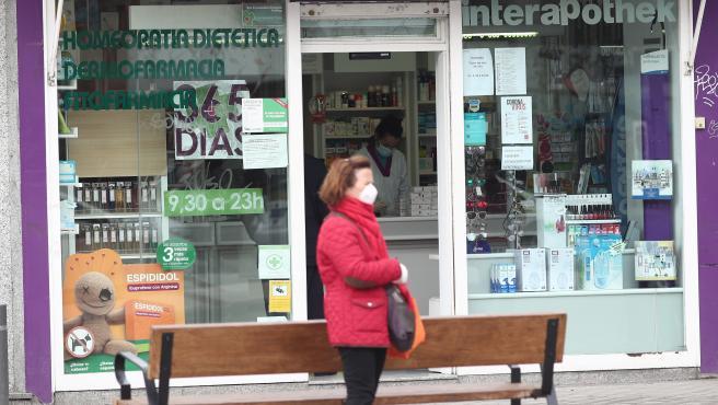 Una mujer protegida con mascarilla pasa al lado de una farmacia abierta en el tercer día laborable del estado de alarma por coronavirus en España, en Madrid (España), a 18 de marzo de 2020.